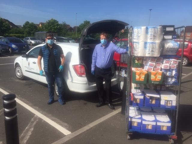 2 men with masks & gloves loading van for food bank