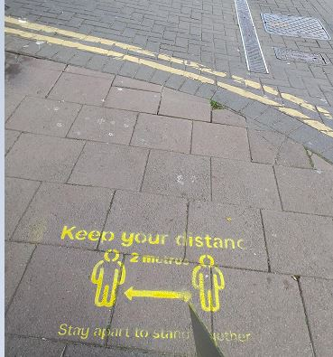 image of social distance stencils on pavement